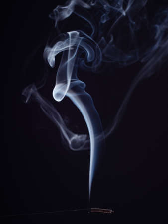 Structure of white smoke, brush effect. Burning incense isolated on black background, close up view. Abstract background of burning sweet smell. Aromatic stick for meditation and relaxation 写真素材