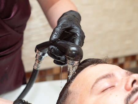 Male in barbershop. Stylist washing males head after hair cutting, close up view. Masters hands in black rubber gloves. Selective soft focus. Blurred background