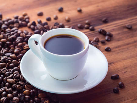 Composition of white coffee cup with black espresso and coffee beans pilled on brown table, close up view. Texture of wooden desk. Selective soft focus. Blurred background