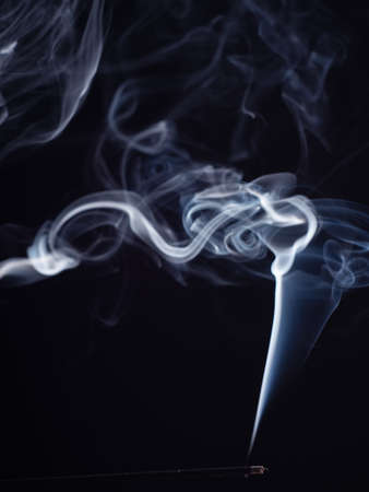 Abstract cloud of white smoke from burning incense, isolated on black background, close up view. Structure of smoke, brush effect. Eastern fragrance for relaxation and meditation