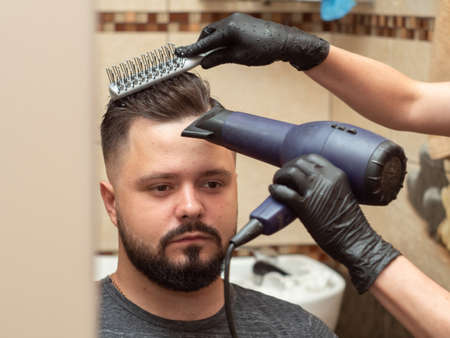 Hairdresser making modern hairdo with hair dryer and round comb, close up view. Stylists hands in black rubber gloves. Male in barbershop. Selective soft focus. Blurred background Imagens