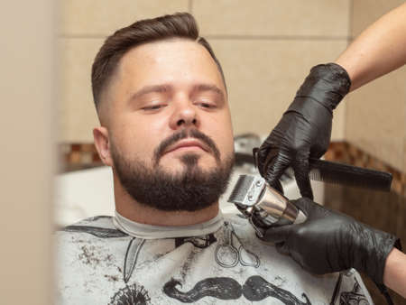 Hairdresser cutting males beaver with clipper and comb, close up view. Stylists hands in black rubber gloves. Photographed in barbershop. Selective soft focus. Blurred background