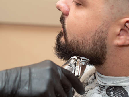 Stylist cutting males beaver with clipper, close up view. Hands in black rubber gloves. Male in hairdressing saloon. Selective soft focus. Blurred background Imagens