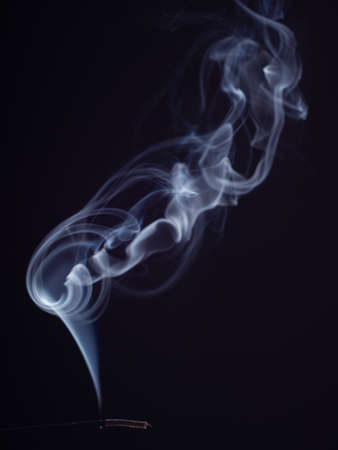 White smoke cloud swirling, isolated on black background, close up view. Abstract background of burning incense, brush effect. Structure of smoke. Eastern fragrance for relaxation and meditation Imagens