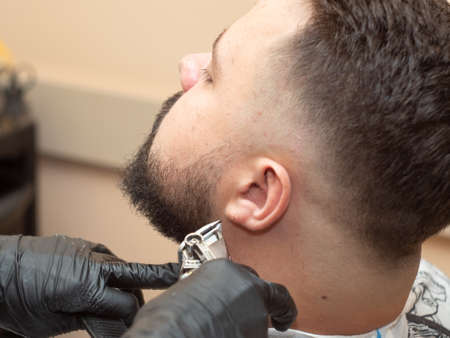 Males beaver cutting with clipper, close up view. Stylists hands in black rubber gloves. Photographed in hairdressing saloon. Selective soft focus. Blurred background Imagens