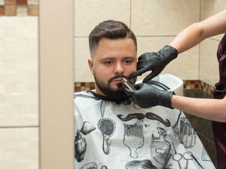 Male in barbershop, close up view. Stylist cutting males beaver with clipper. Hands in black rubber gloves. Stylist and client reflecting in mirror. Selective soft focus. Blurred background