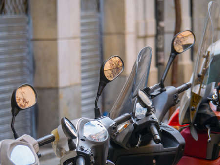 close up view on motor cycles parked near building. Row of bikes. Parking in Barcelona. Selective soft focus. Blurred background