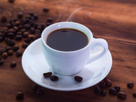 Coffee cup with espresso and coffee beans pilled on brown table, close up view. Texture of brown wooden table. Selective soft focus. Blurred background Imagens