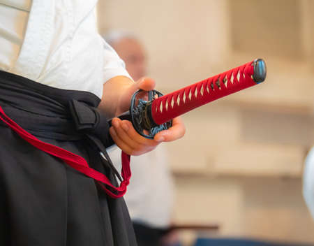 Man dressed in keikogi and hakama stay with japanese sword close up. Martial arts instructor with katana on seminar. View of front. Banco de Imagens