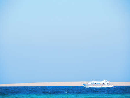 White boat with tourists sailing Red Sea, long view. Blue sky is clear. Photographed in Egypt in february. Selective soft focus. Blurred background