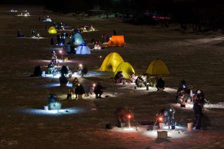 handline fishing: fishing men at night during winter Stock Photo