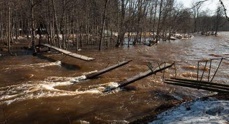 pedestrian bridge: flooding in river wit broken pedestrian bridge Stock Photo