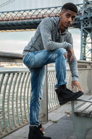 A portrait of a young, black man, pensively standing along New York City's East River and Williamsburg Bridge.