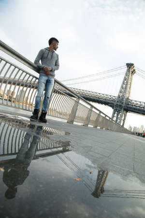 A young, black man walks along New York Citys East River with Brooklyns Williamsburg Bridge in the background. Shot during the Autumn of 2016. Stock Photo