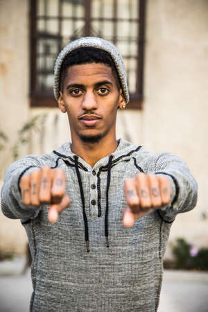 A portrait of a young, black man showing off the tattoos on the knuckles of his hands. Model Released and shot during the autumn of 2016.