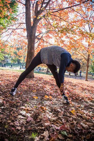 A young, athletic man stretches in the park before a run. Foliage lays around the man during the Autumn of 2016. Stock Photo