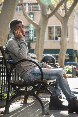 A candid portrait of a young, black man using his phone in New York City. Shot during the autumn of 2016.