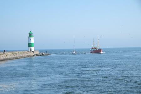 Trawler next to lighthouse