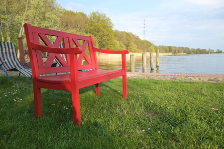 Red bench by the water