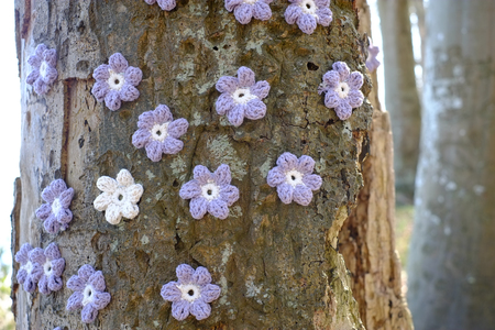 Embroidered flowers on a tree trunk Фото со стока