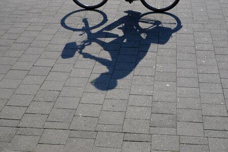 Cyclist casts shadows on the bike path Stok Fotoğraf