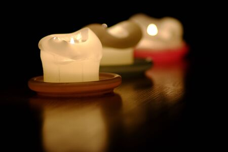 Three candles are reflected on a tabletop Stok Fotoğraf