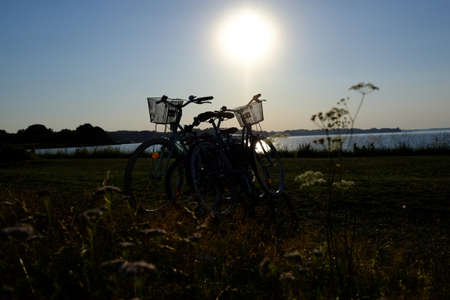 Two bicycles can be seen on a lake at dusk