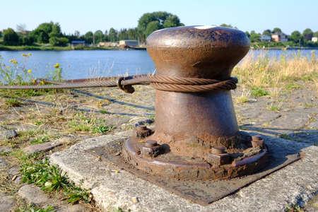 Rusty steel bollard on the harbor wall Standard-Bild
