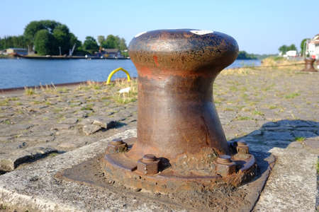 Rusty steel bollard with a rusty steel hawser