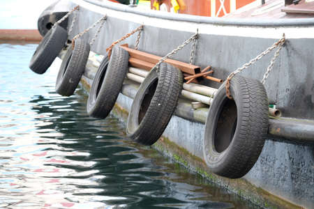 Car tires are attached to the outside of a ship's hull for protection Standard-Bild