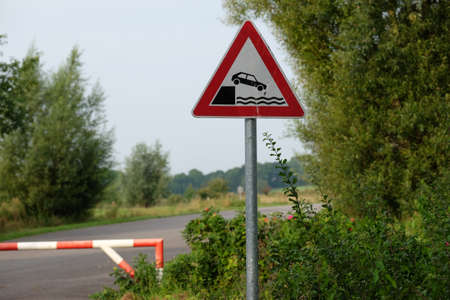 Warning sign - a car can fall into the water here Standard-Bild