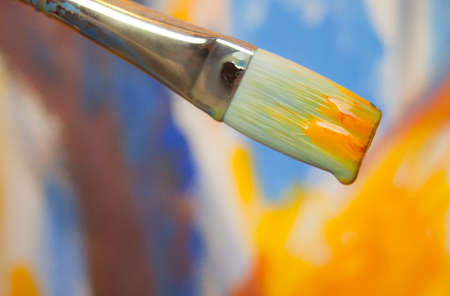 Paint brush dipped in bright paint