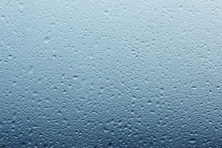Water droplets on the glass with a blue color gradient Stock Photo