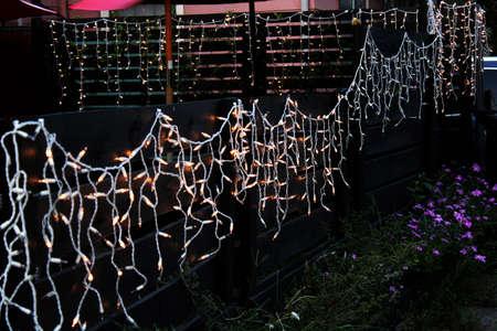 festive lighting cascades along a fence Stockfoto