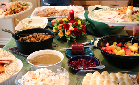 Casual Thanksgiving Dinner on Table With Family Filling Plates