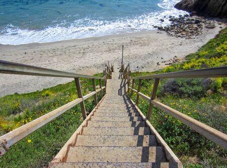 Steel Stairs Descend onto Malibu California Beach with Sand and Sea Stock Photo