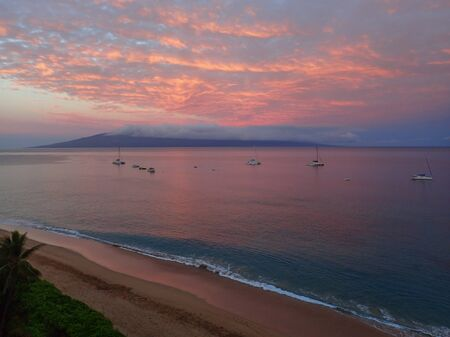 Morning Sunrise Aerial View over Maui Hawaii Beach with Pink Clouds Reflected on Vast Ocean and Island in Background 版權商用圖片