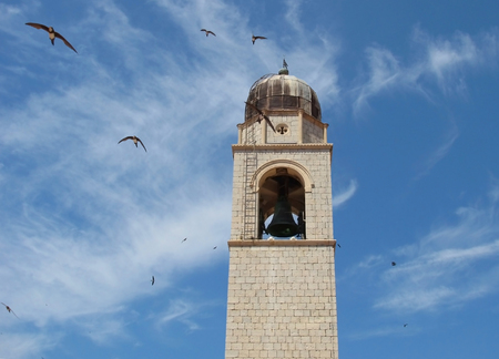 Bell Tower Reaches Towards Blue Sky as Swallows Fly Reklamní fotografie - 89129925