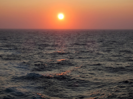 Zonsondergang die over Ruwe Oceaanoppervlakte gloeien Stockfoto