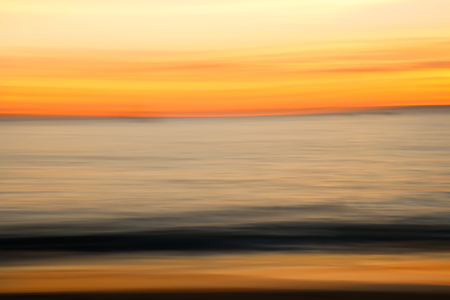 Bright Motion Blur Sunset over Ocean and Beach Stock Photo