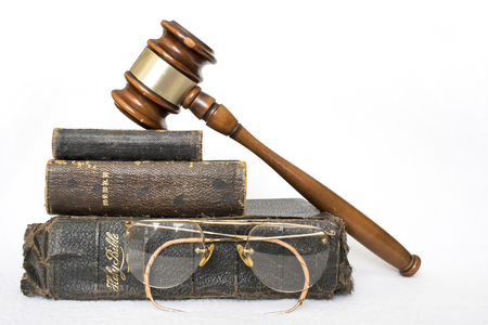 Stack of Three Antique Worn Leather Bibles with Antique Glasses and Gavel on White Background