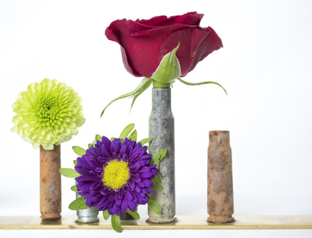 Bullet Casings As Bud Vases Hold Red Rose And Flowers With One
