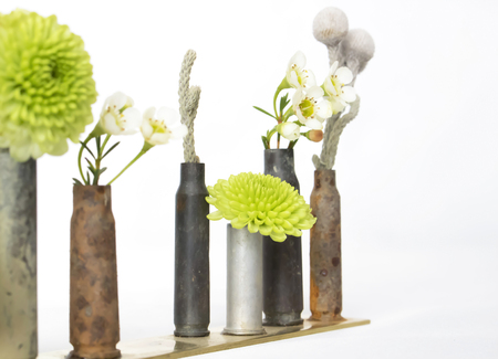 Diagonal Close Up Row of Used Bullet Shells Holding Flowers Stock Photo