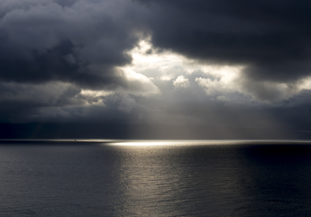 Sunlight Breaks Through Storm Clouds over Ocean Imagens