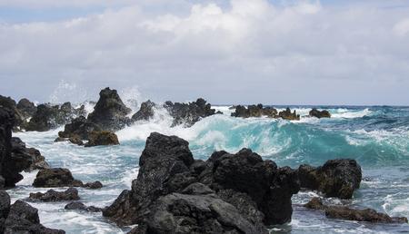 Turquoise Ocean Wave Breaks on Lava Rocks