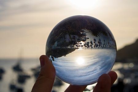 Sunrise over port with boats captured in reflection in glass ball