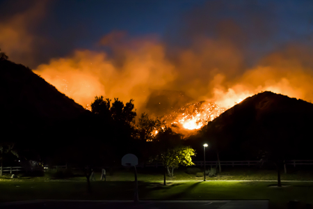 Bright Orange Flames Burning Hills Behind Neighborhood Park During California Fire Stockfoto