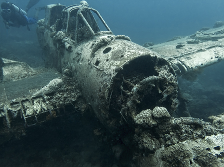 Jake seaplane wreck from World War 2 sits on ocean floor with diver swimming by in Palau.