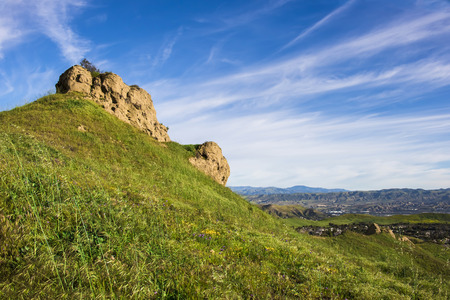 Foothills rise above California suburbs with bright colored growth under blue sky. Stock Photo