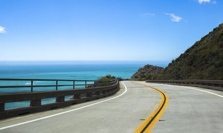 Road leads along coast of California on Highway 1 with curving pavement and guard rails over bright blue water.